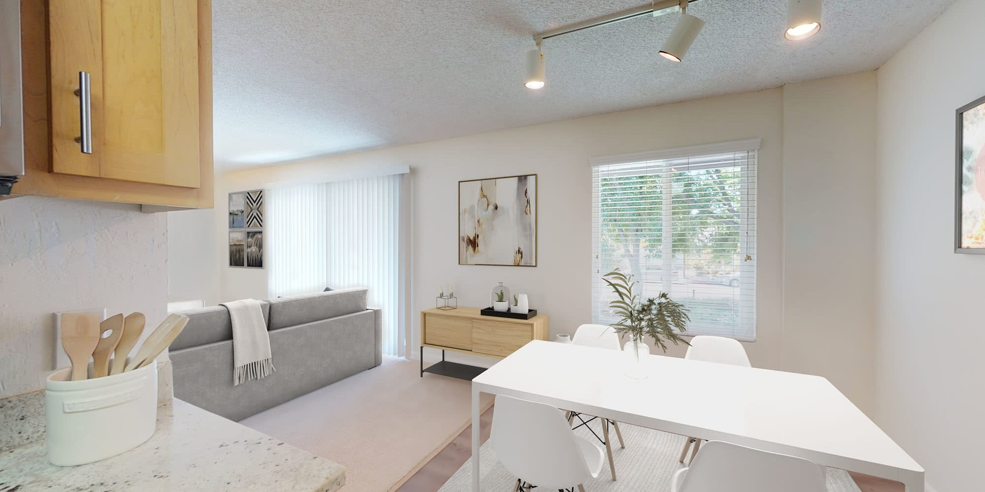 Dining and living areas in an open-concept model home at Pleasanton Glen Apartment Homes in Pleasanton, California