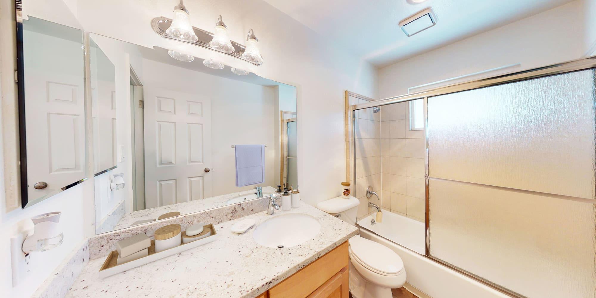 Large vanity mirror in a model apartment's well-lit primary bathroom at Pleasanton Glen Apartment Homes in Pleasanton, California