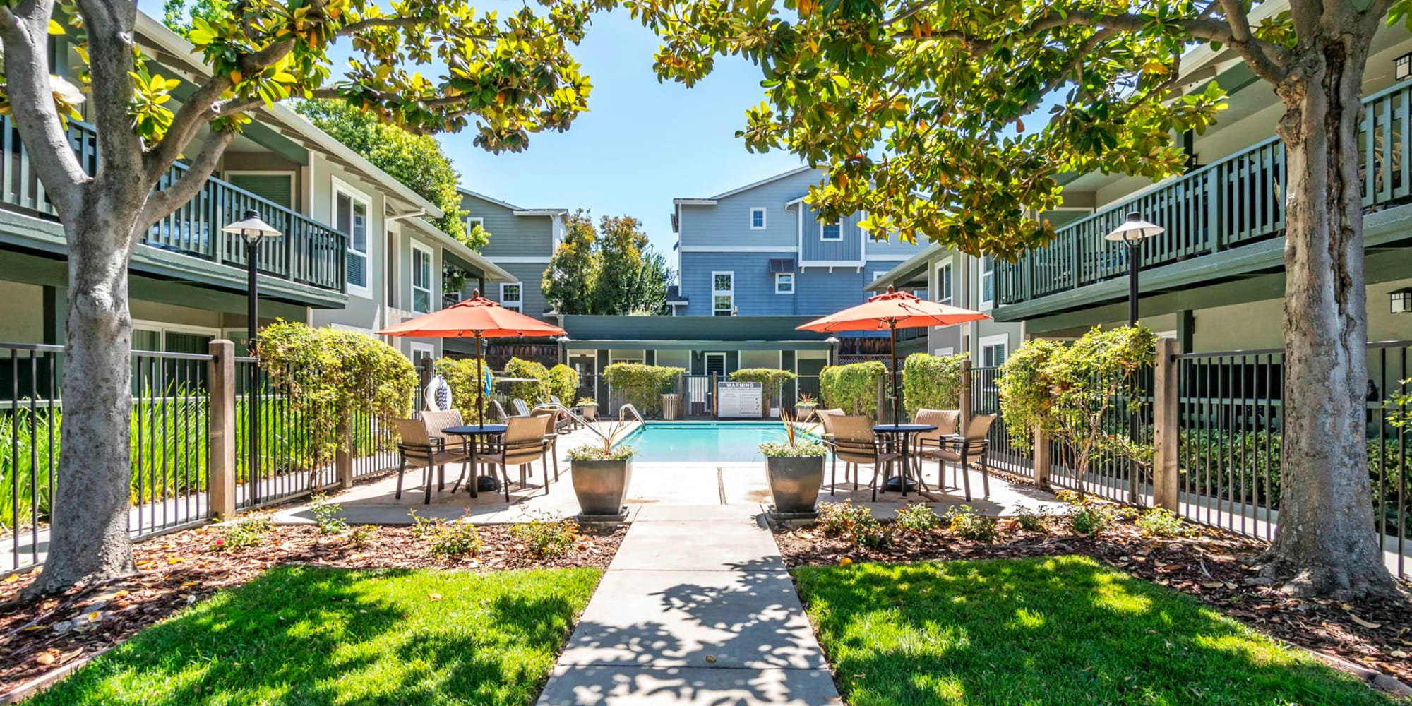 Shaded pathway leading to the swimming pool area at Pleasanton Glen Apartment Homes in Pleasanton, California