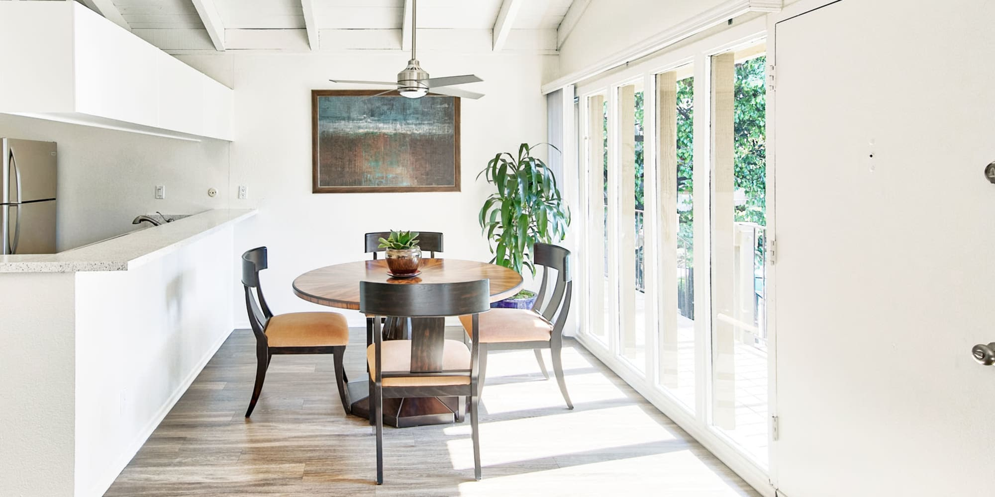 Floor-to-ceiling windows in the dining area next to the private balcony outside a model home at Mediterranean Village Apartments in Costa Mesa, California