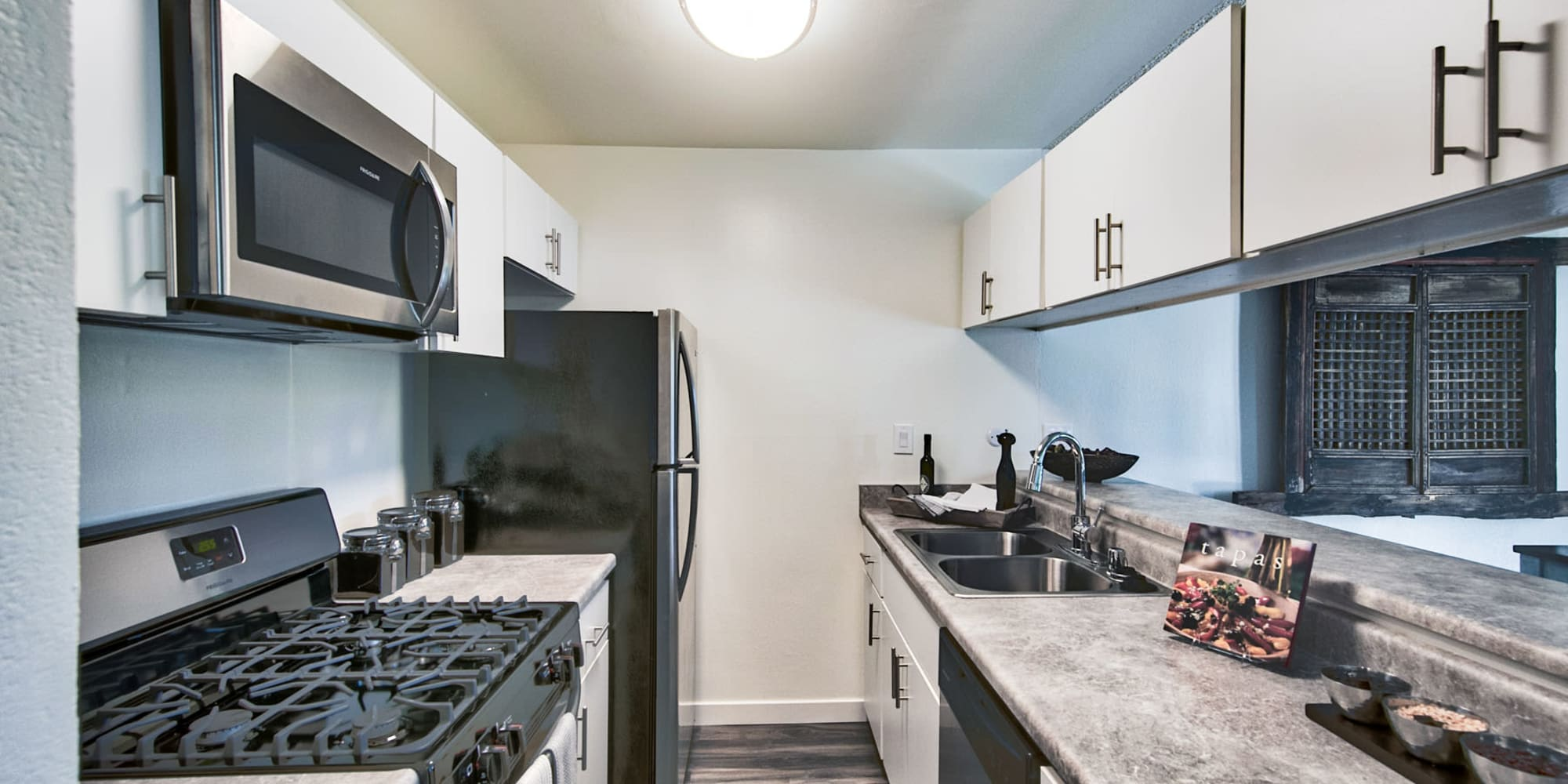Stainless-steel appliances and granite countertops in a model apartment's kitchen at Mediterranean Village Apartments in Costa Mesa, California