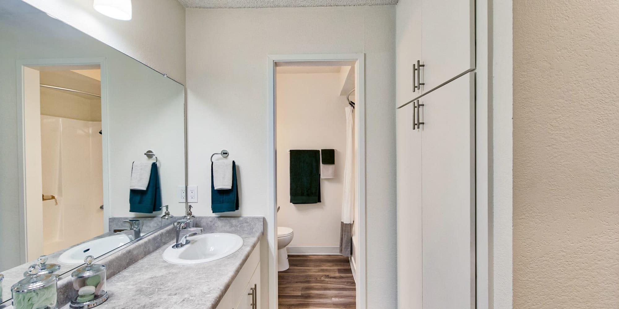Large vanity mirror and a granite countertop in a model apartment's bathroom at Mediterranean Village Apartments in Costa Mesa, California