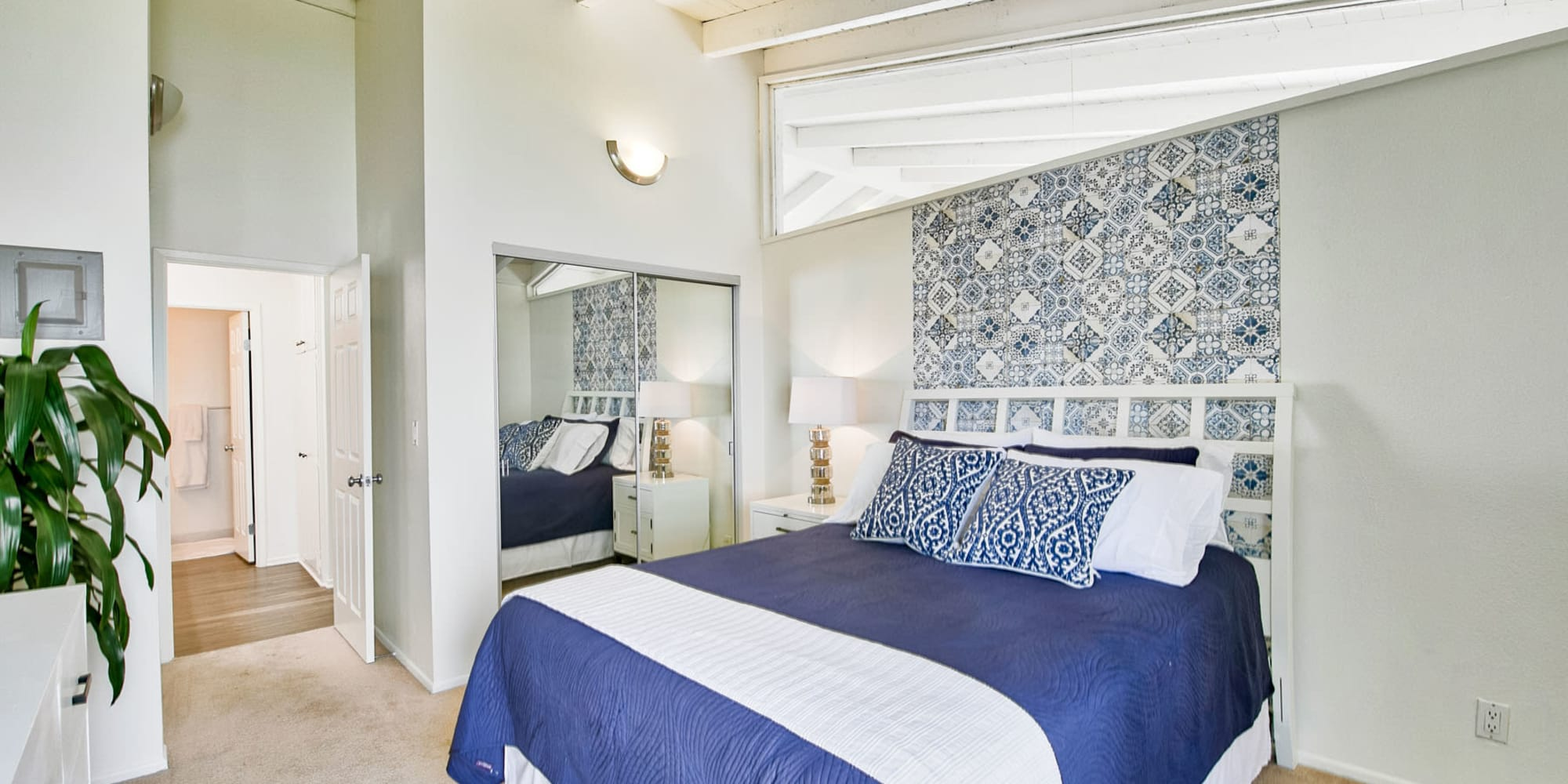 Plush carpeting and modern furnishings in a model home's bedroom at Mediterranean Village Apartments in Costa Mesa, California