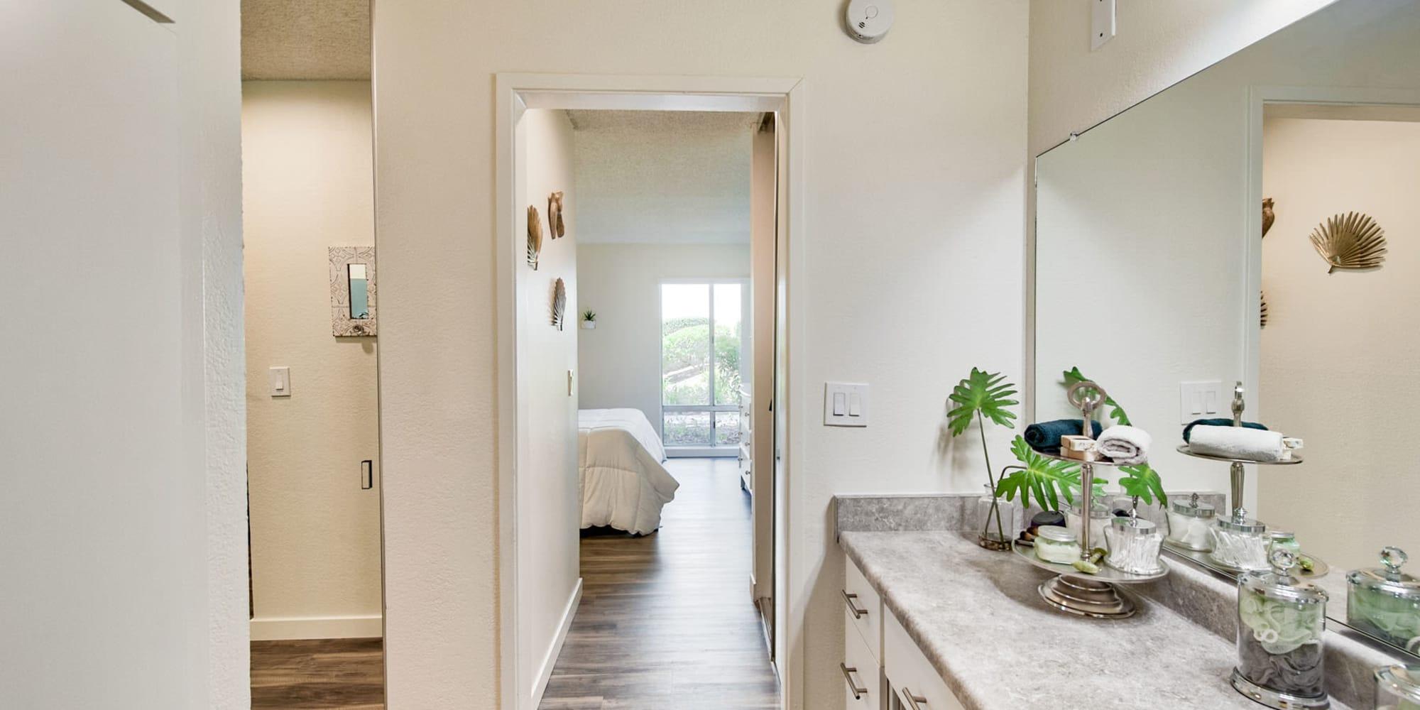 Hardwood flooring throughout a model home's primary bedroom and en suite bathroom at Mediterranean Village Apartments in Costa Mesa, California
