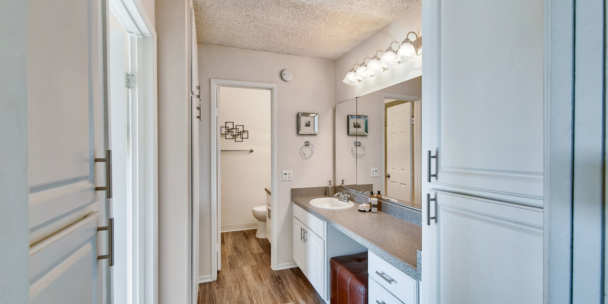 Hardwood flooring and extra storage in a model home's bathroom at Mediterranean Village Apartments in Costa Mesa, California