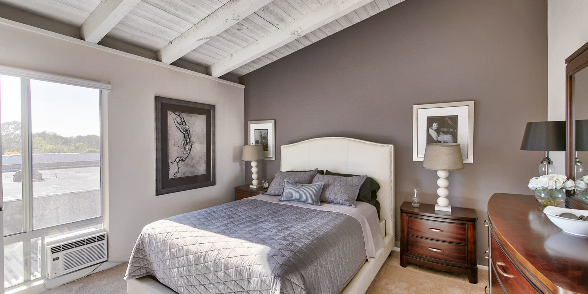 Accent wall and vaulted ceiling in a model apartment's primary bedroom at Mediterranean Village Apartments in Costa Mesa, California