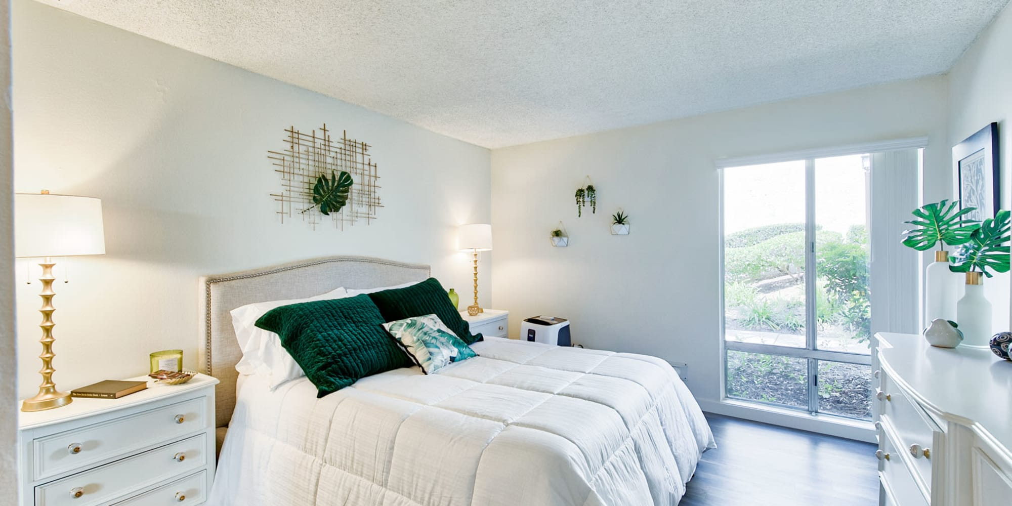 Large bay windows filling a model home's primary bedroom with natural light at Mediterranean Village Apartments in Costa Mesa, California