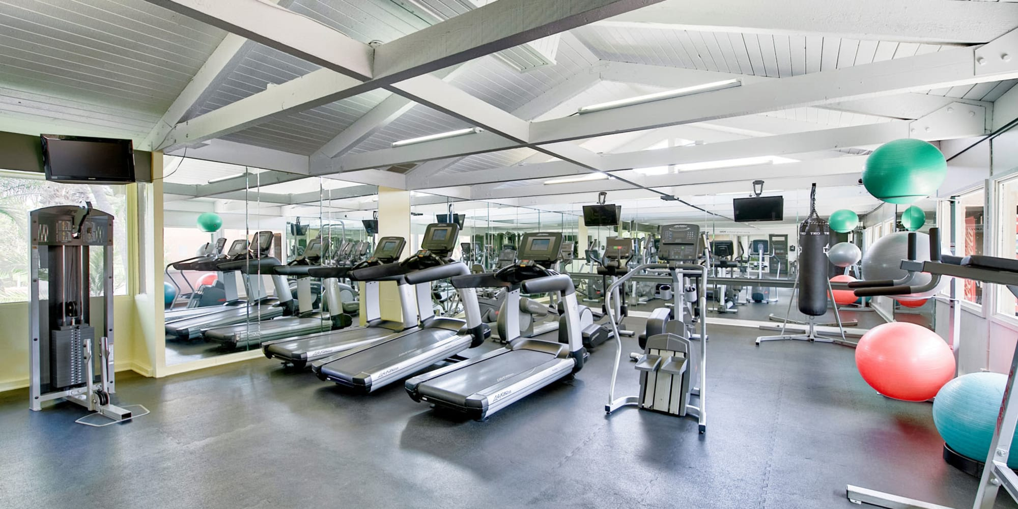 Ample cardio equipment and more in the well-equipped fitness center at Mediterranean Village Apartments in Costa Mesa, California