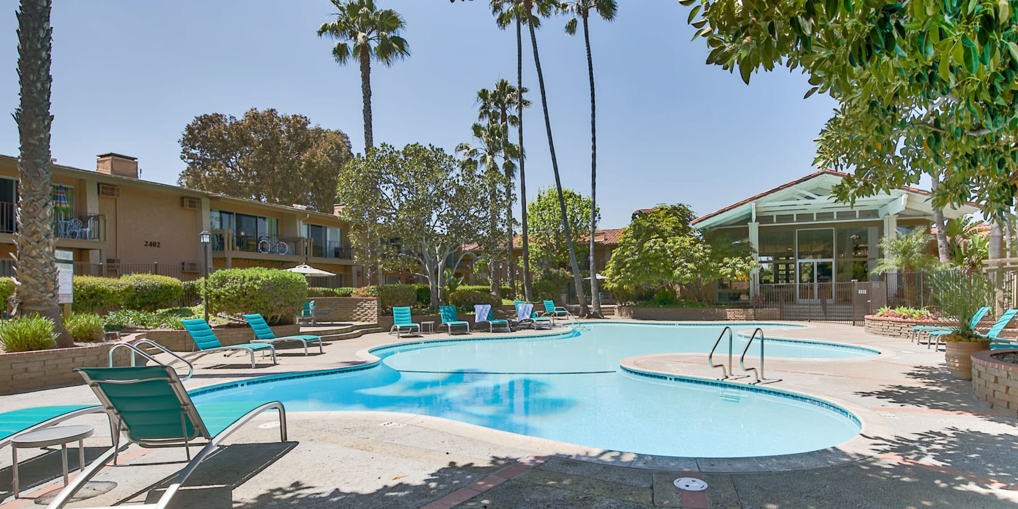 Palm trees and lounge chairs around the swimming pool at Mediterranean Village Apartments in Costa Mesa, California