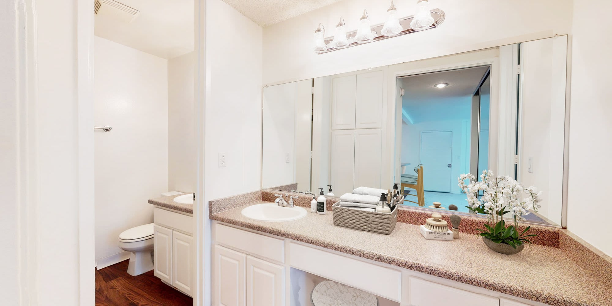 Well-lit bathroom with a large vanity mirror in a model home at Mariners Village in Marina del Rey, California