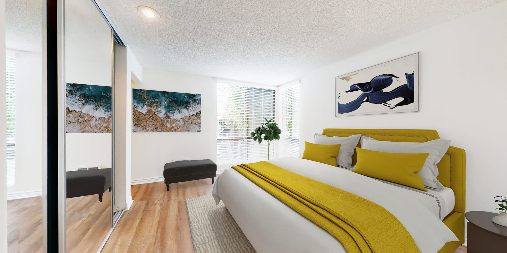 Hardwood flooring and mirrored closet doors in a model apartment's bedroom at Mariners Village in Marina del Rey, California