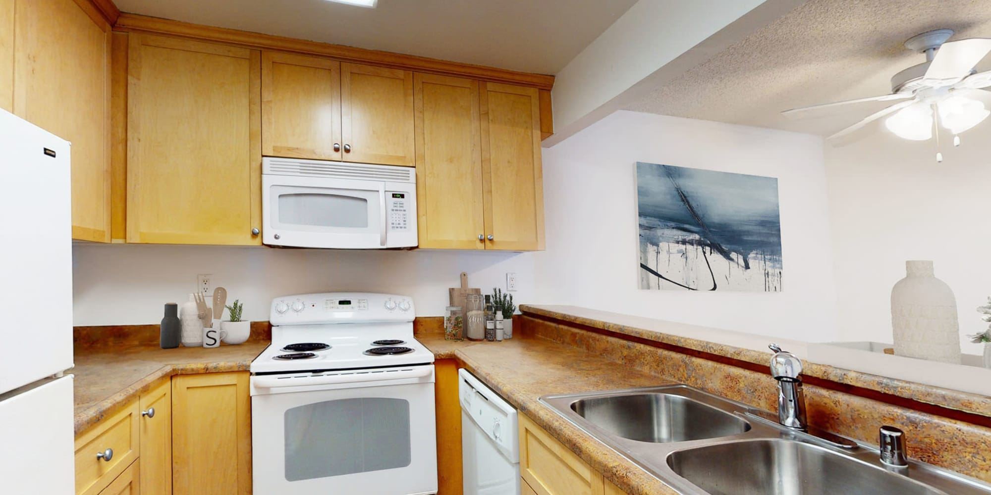 Wood cabinetry and a dual-basin sink in a model home's kitchen at Mariners Village in Marina del Rey, California