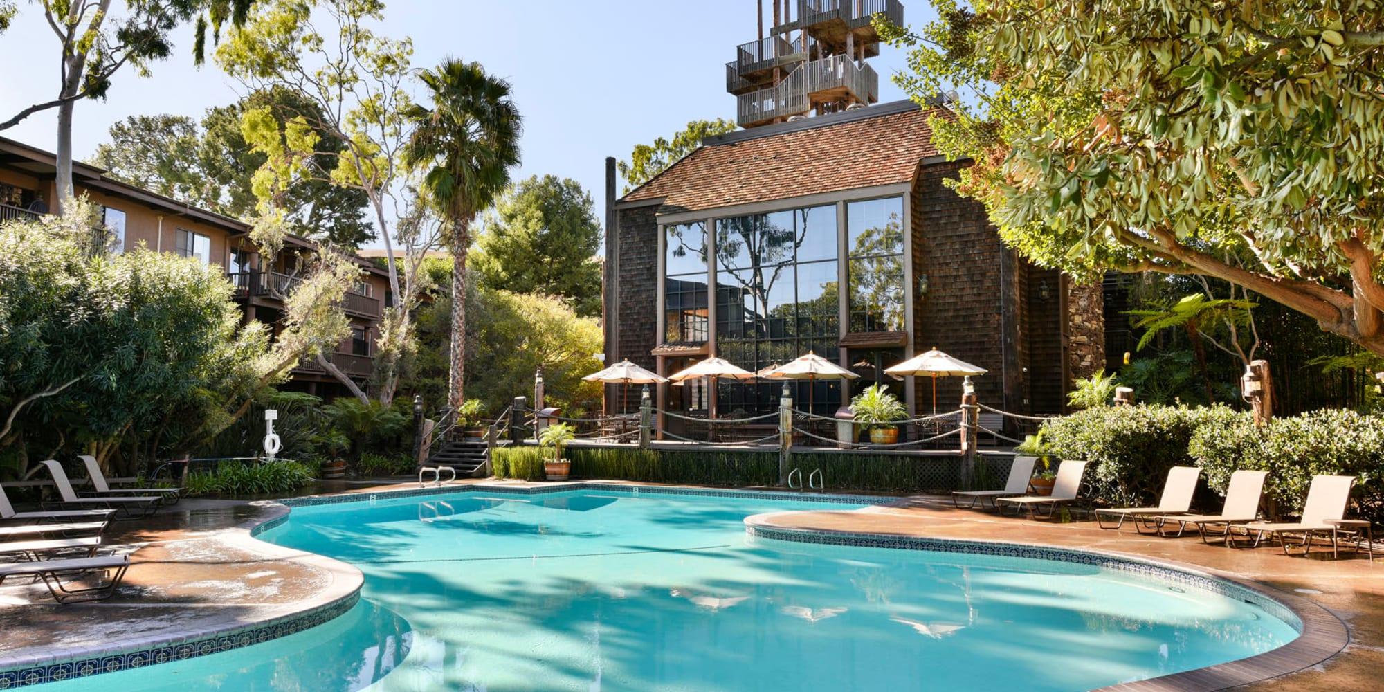 Resort-style swimming pool surrounded by mature trees at Mariners Village in Marina del Rey, California