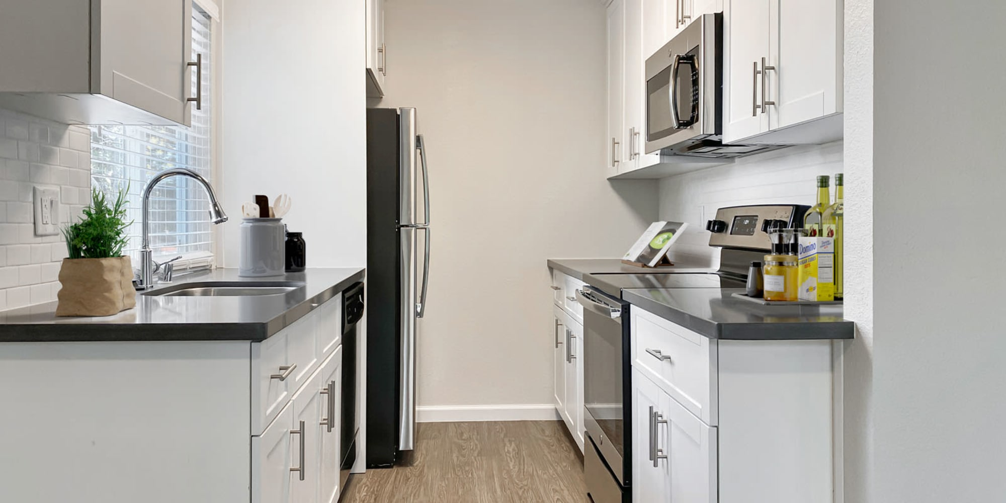 Stainless-steel appliances and bright white cabinetry in a model home's kitchen at Valley Plaza Villages in Pleasanton, California
