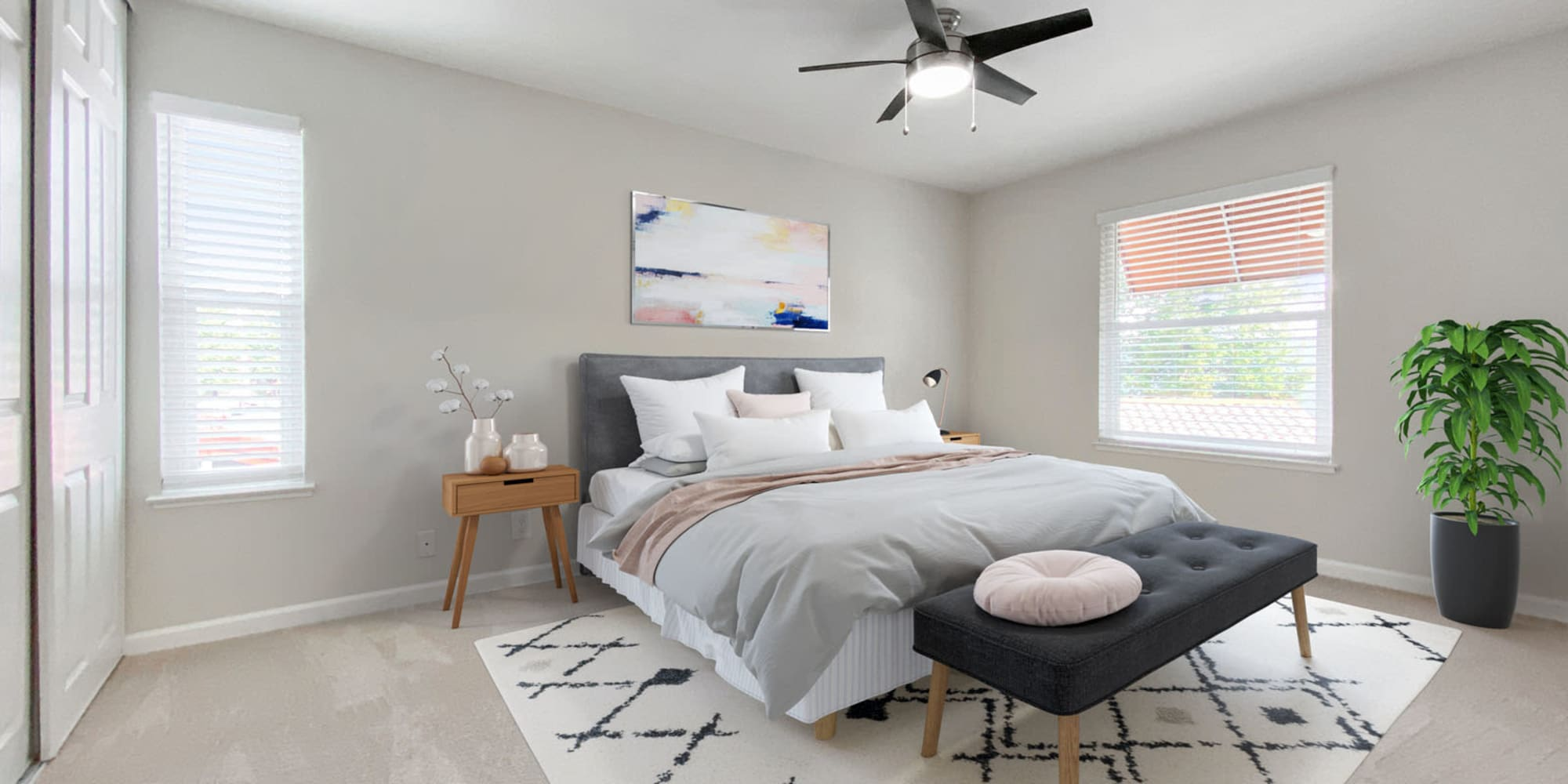 Ceiling fan, plush carpeting, and bay windows in a model apartment's primary bedroom at Valley Plaza Villages in Pleasanton, California