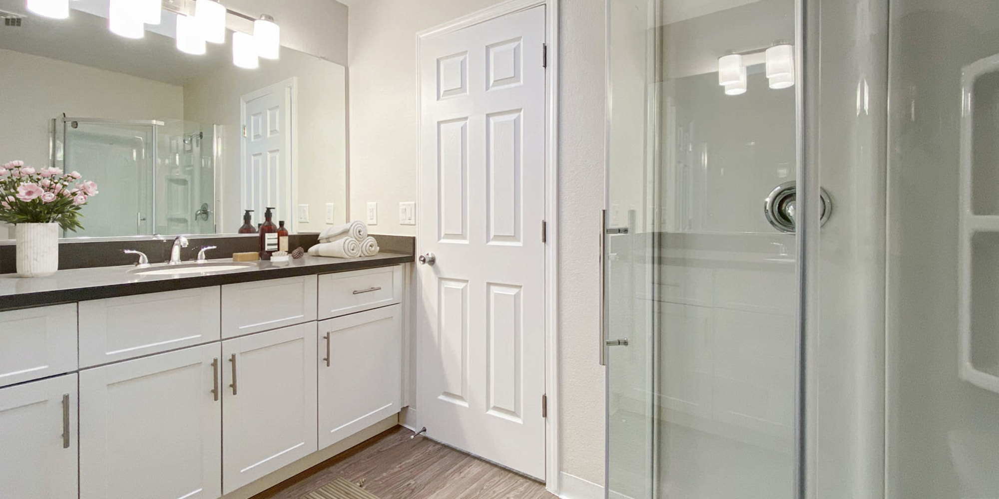 Ample storage space and glass shower doors in a model apartment's bathroom at Valley Plaza Villages in Pleasanton, California