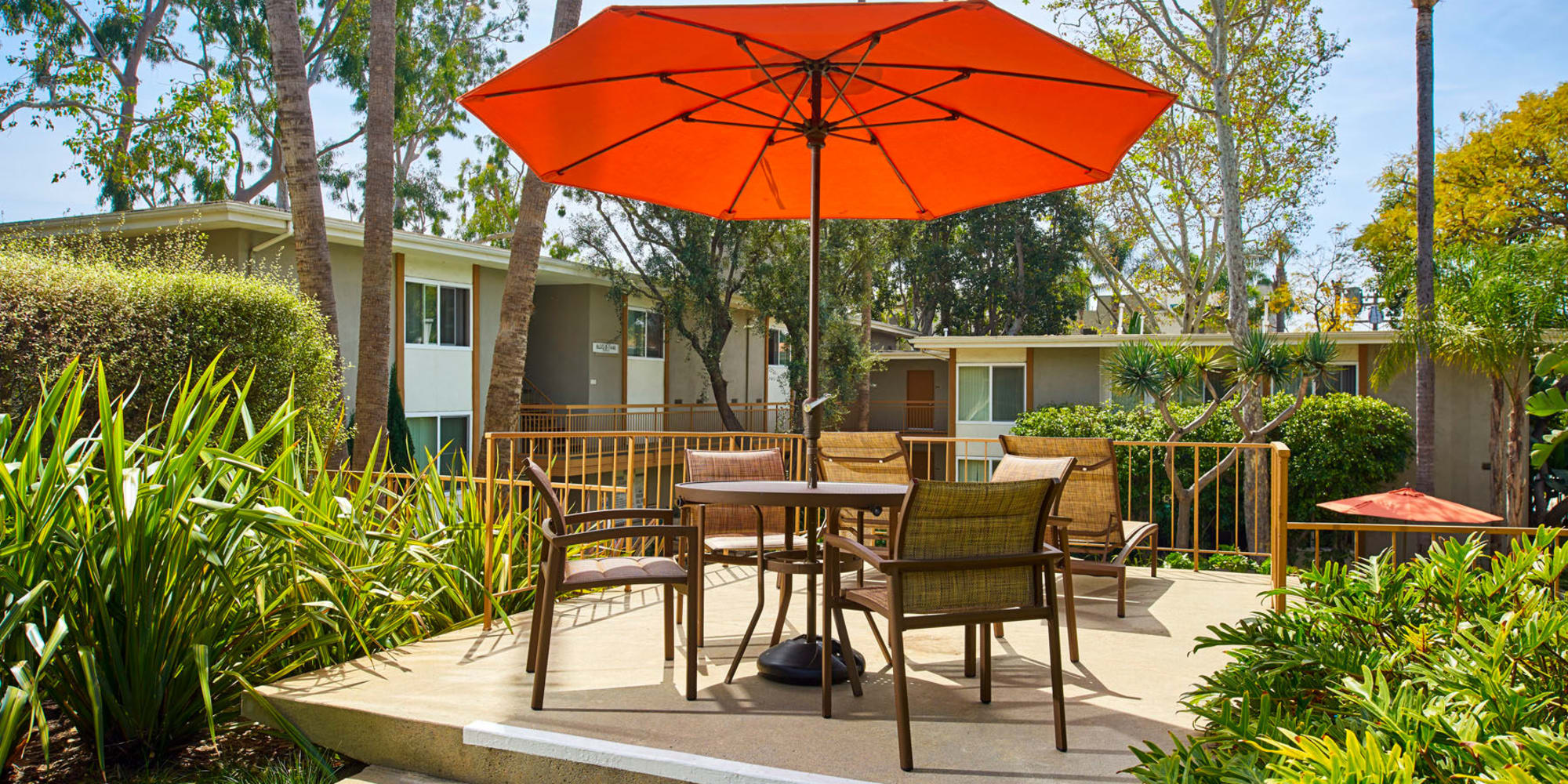 Umbrella providing shade to an outdoor seating area surrounded by lush landscaping at West Park Village in Los Angeles, California