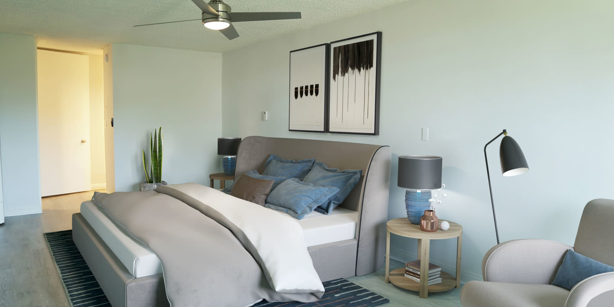 Well-furnished model home's primary bedroom with a ceiling fan at Casa Granada in Los Angeles, California