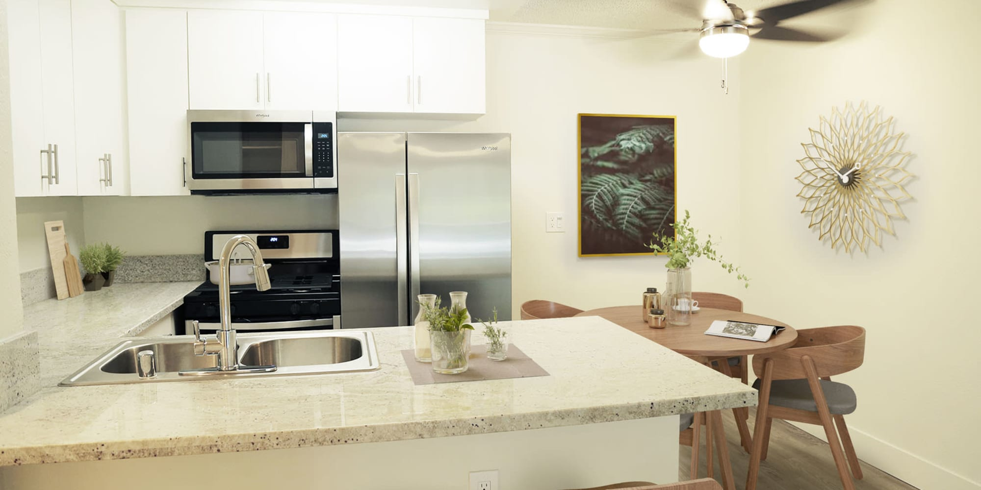 Stainless-steel appliances and granite countertops in a model home's kitchen at Casa Granada in Los Angeles, California