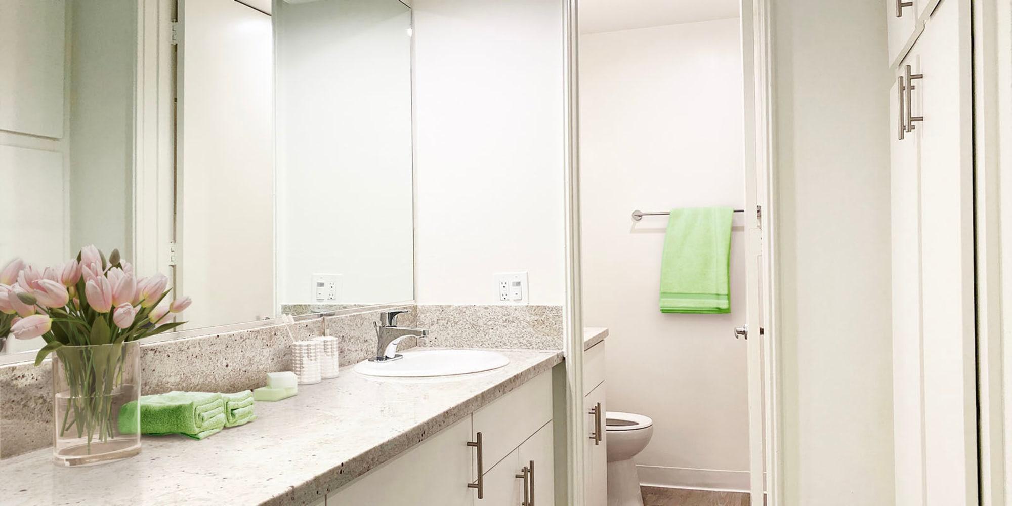 Model home's bathroom with extra storage and a granite countertop at Casa Granada in Los Angeles, California