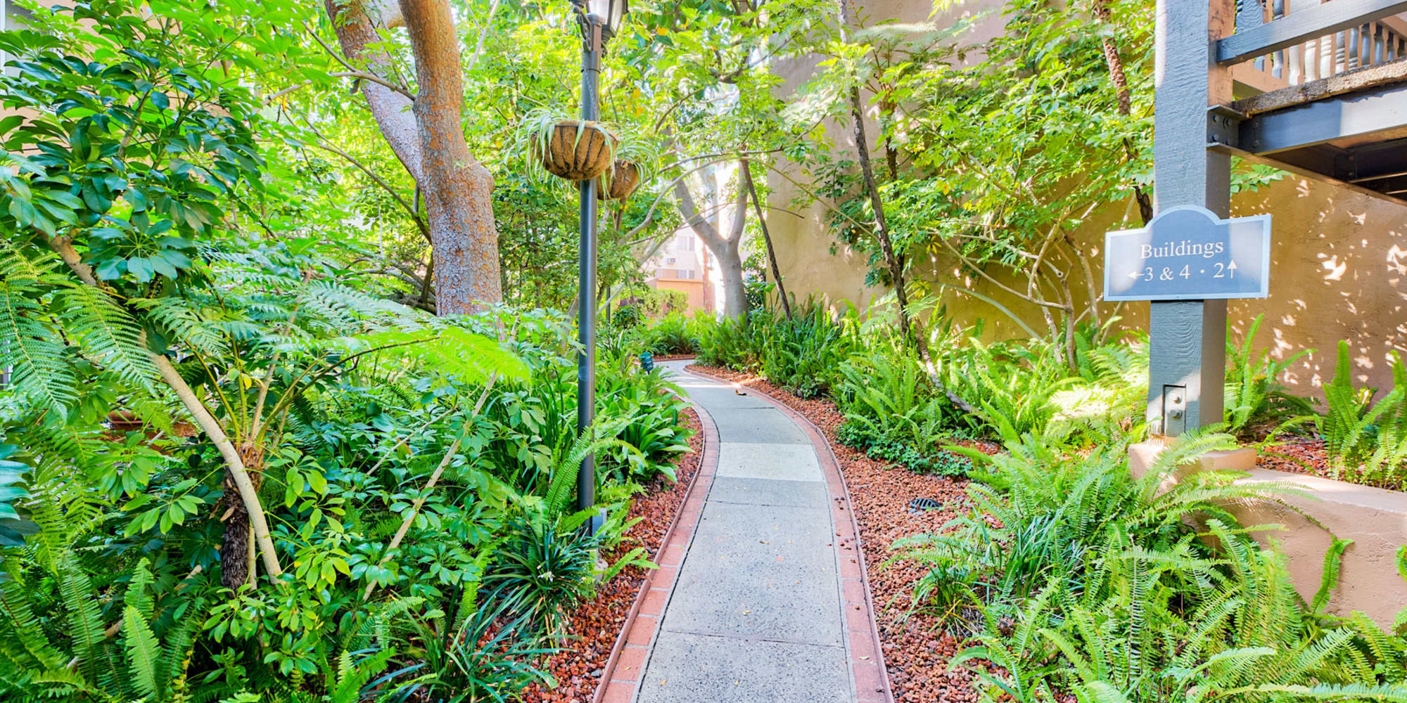 Well-maintained pathway through the lush garden-style landscaping at Casa Granada in Los Angeles, California
