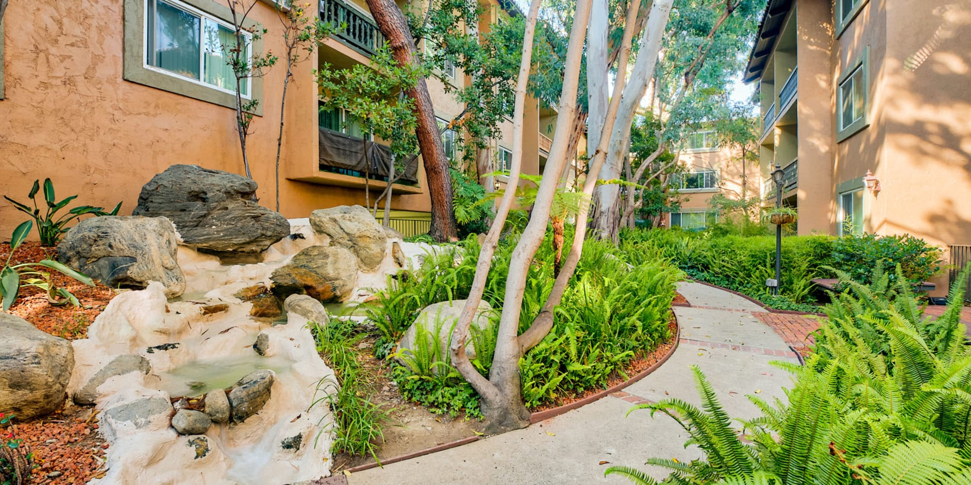 Water feature spilling down the rocks next to a path through the community at Casa Granada in Los Angeles, California