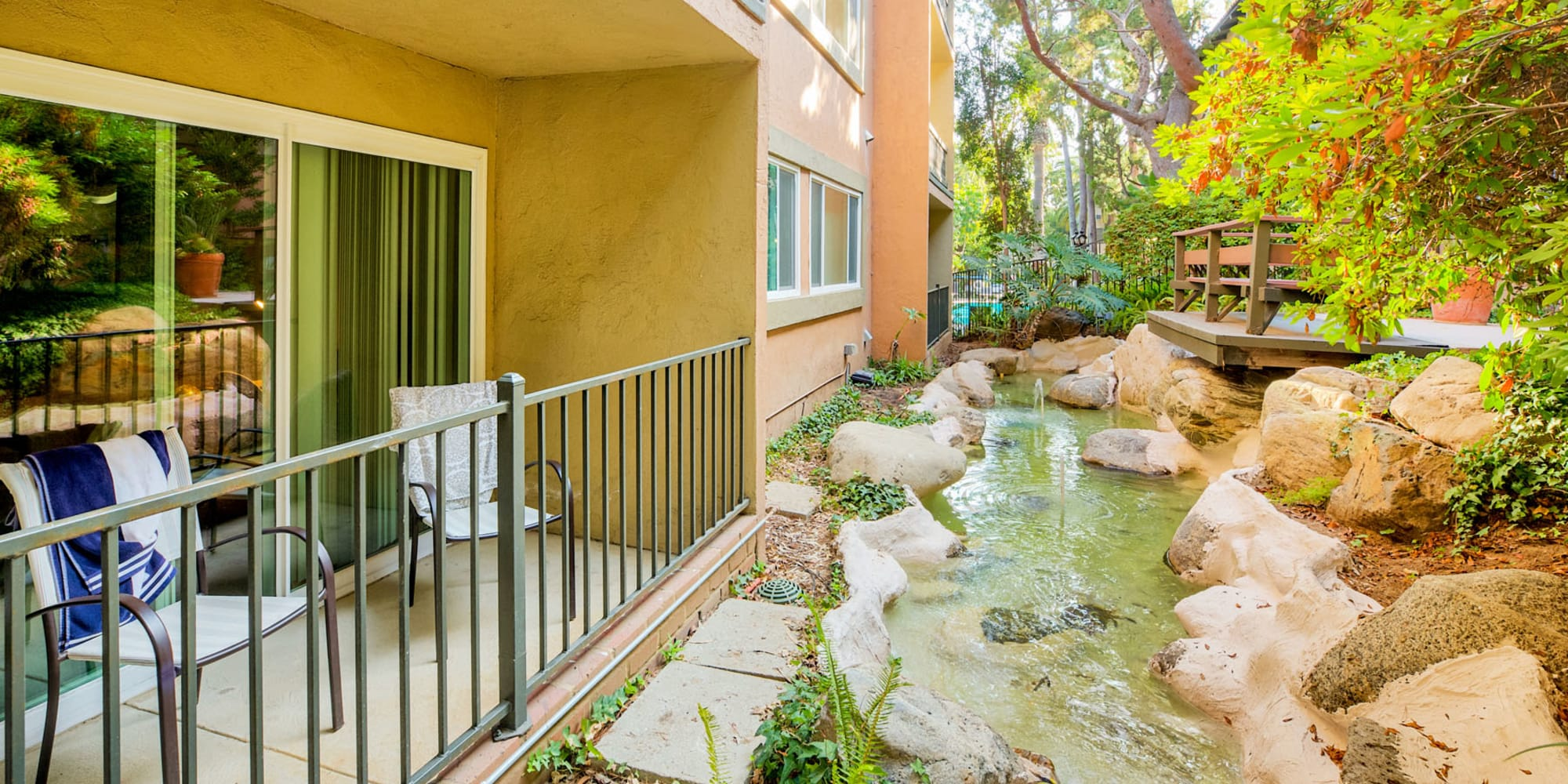 Private patio outside a resident apartment overlooking a water feature at Casa Granada in Los Angeles, California