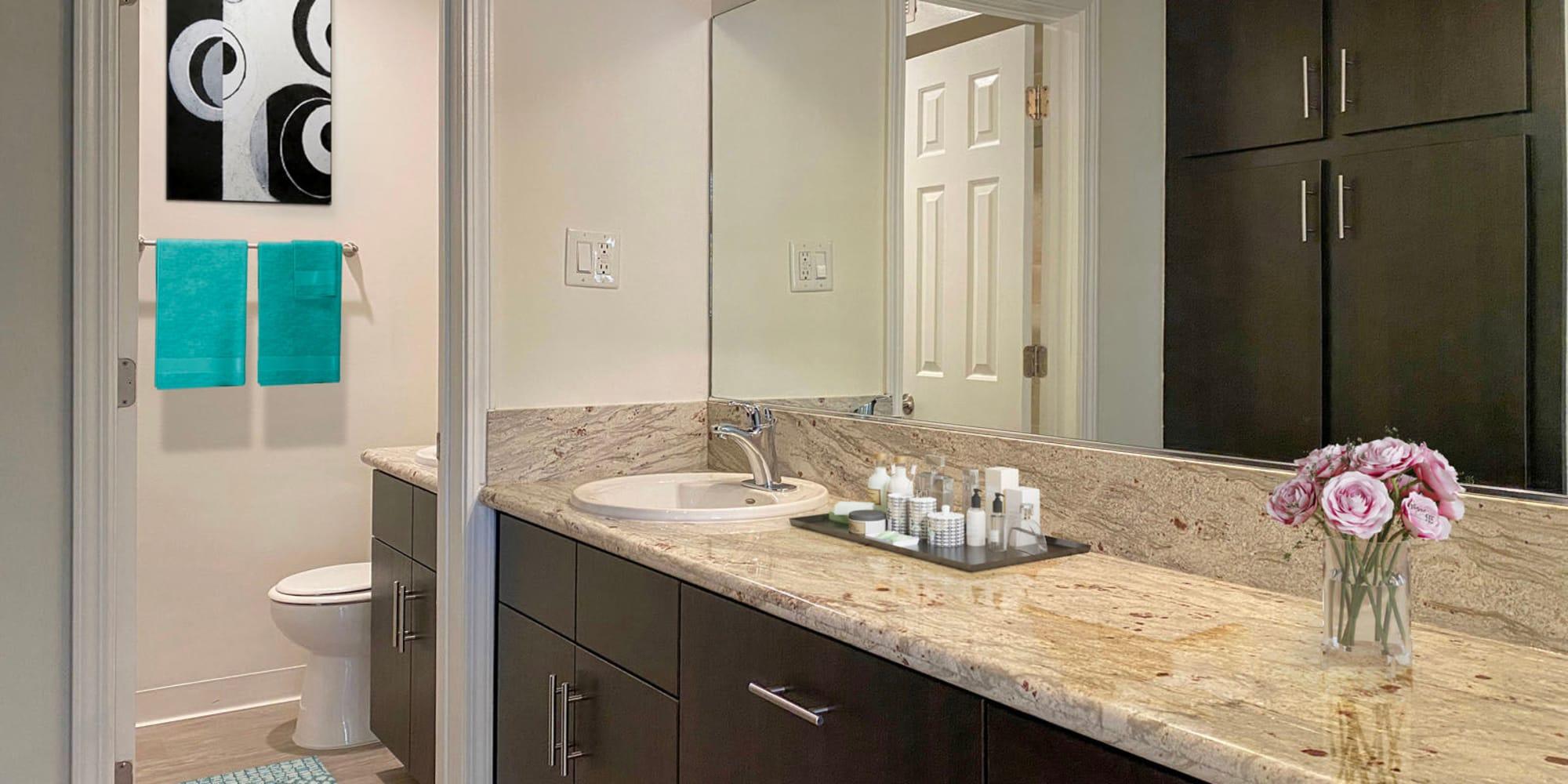 Spacious granite countertop in a model apartment's bathroom at Mediterranean Village in West Hollywood, California