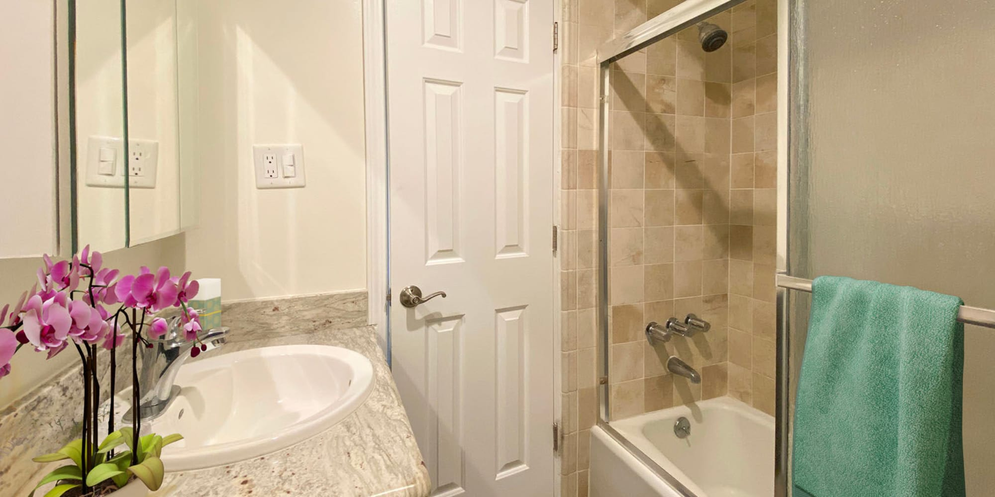 Tiled shower and a granite countertop in a model home's bathroom at Mediterranean Village in West Hollywood, California