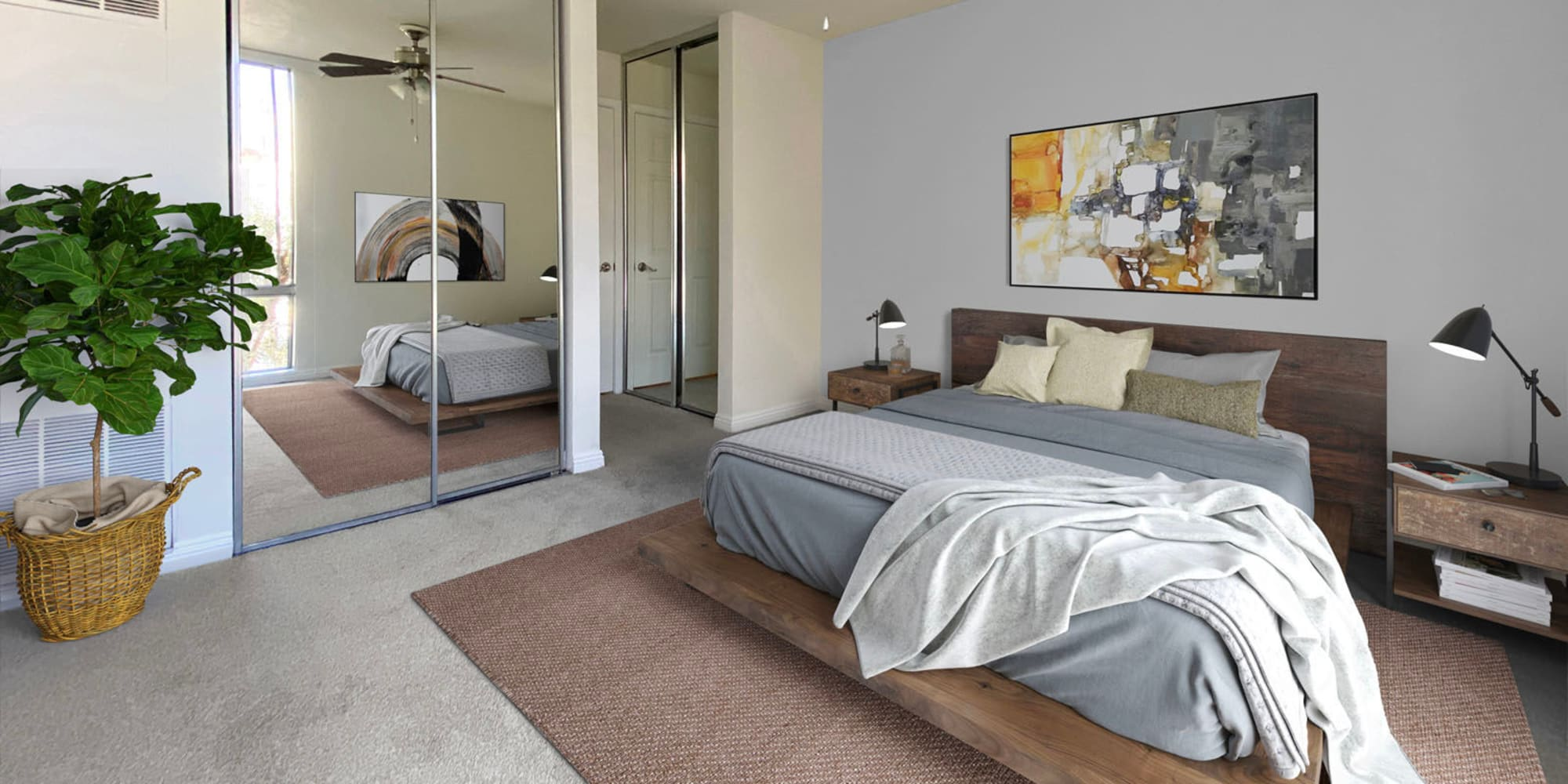 Model home's primary suite with mirrored closet doors and contemporary furnishings at Mediterranean Village in West Hollywood, California