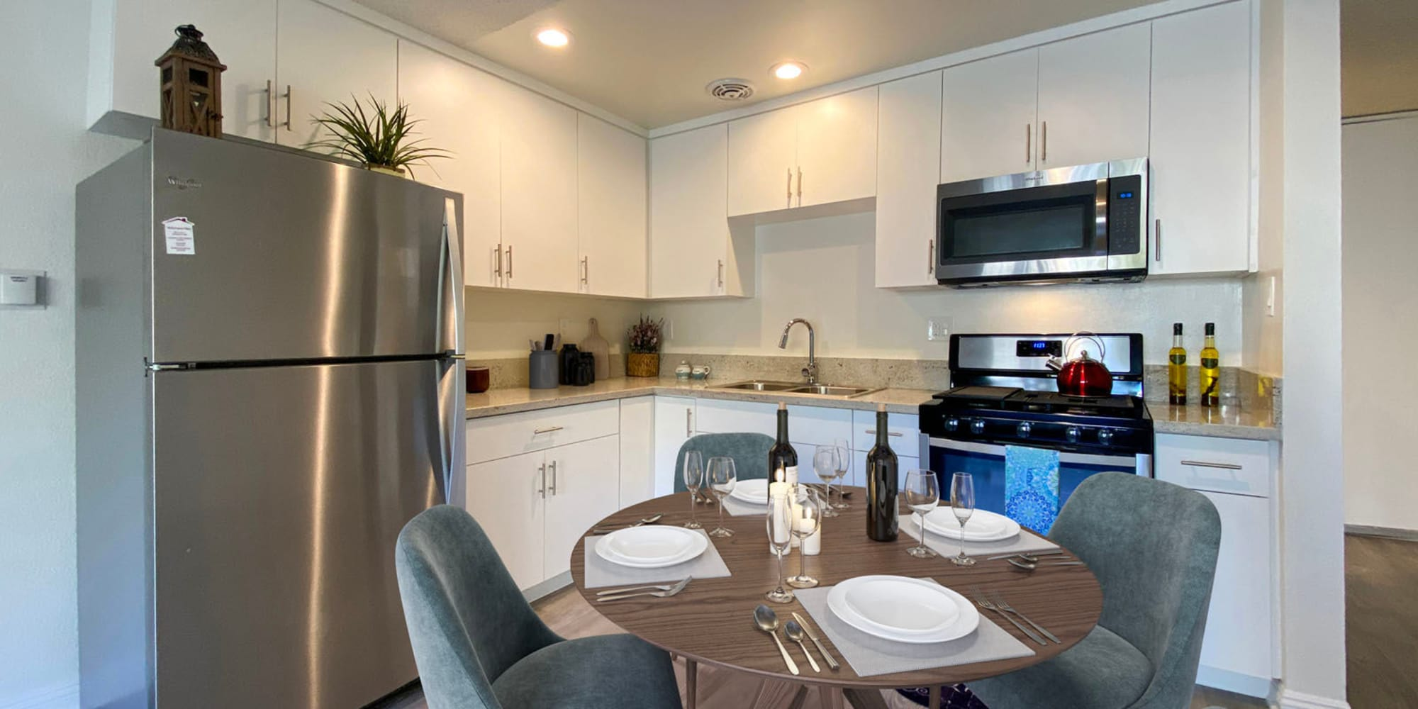 Dining area next to the open-concept kitchen in a model apartment at Mediterranean Village in West Hollywood, California