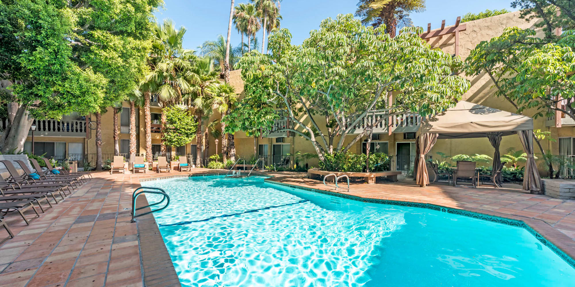 Lounge chairs and lush landscaping around the swimming pool at Mediterranean Village in West Hollywood, California