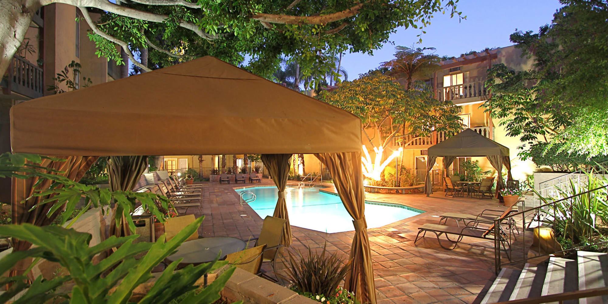 Dusk view of the swimming pool area with covered cabanas at Mediterranean Village in West Hollywood, California