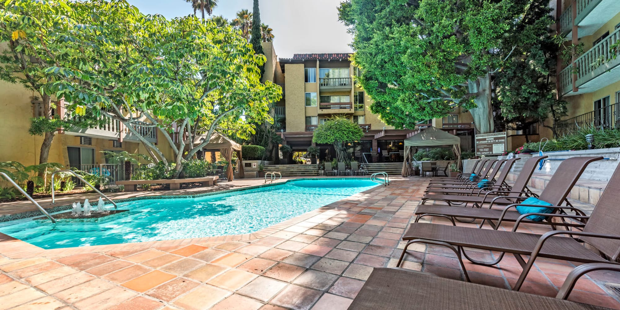 Chaise lounge chairs flanking the pool at Mediterranean Village in West Hollywood, California