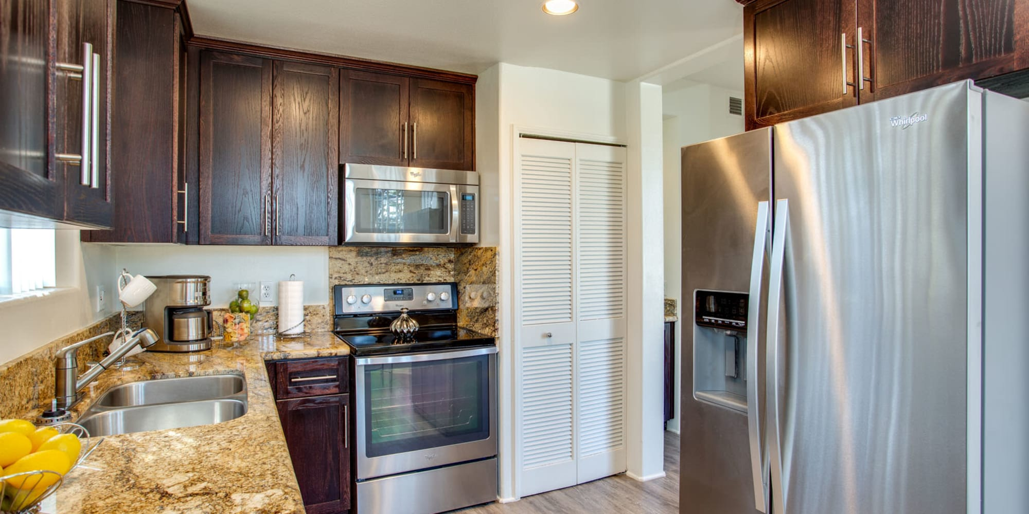 Stainless-steel appliances and a dual-basin sink in a model home's kitchen at L'Estancia in Studio City, California