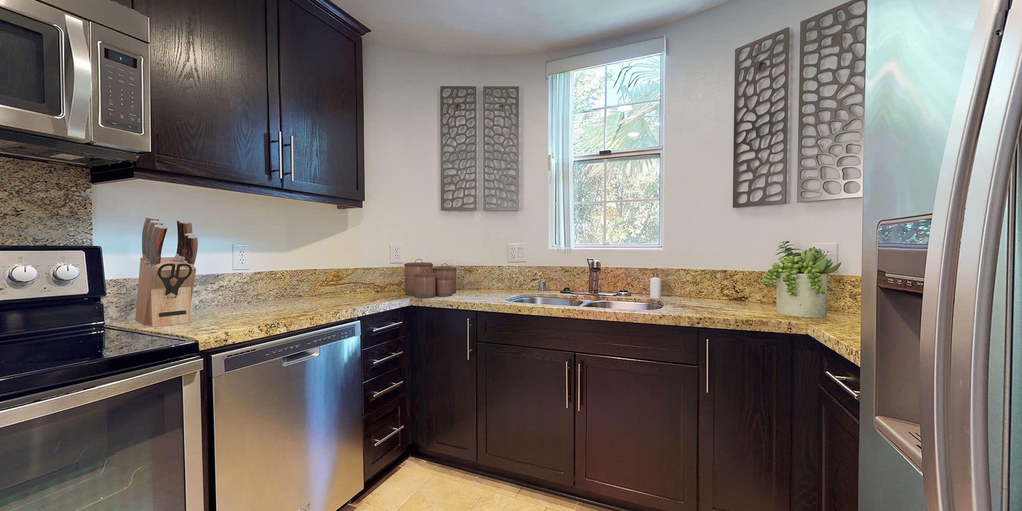 Granite countertops and espresso wood cabinetry in a model apartment's kitchen at L'Estancia in Studio City, California