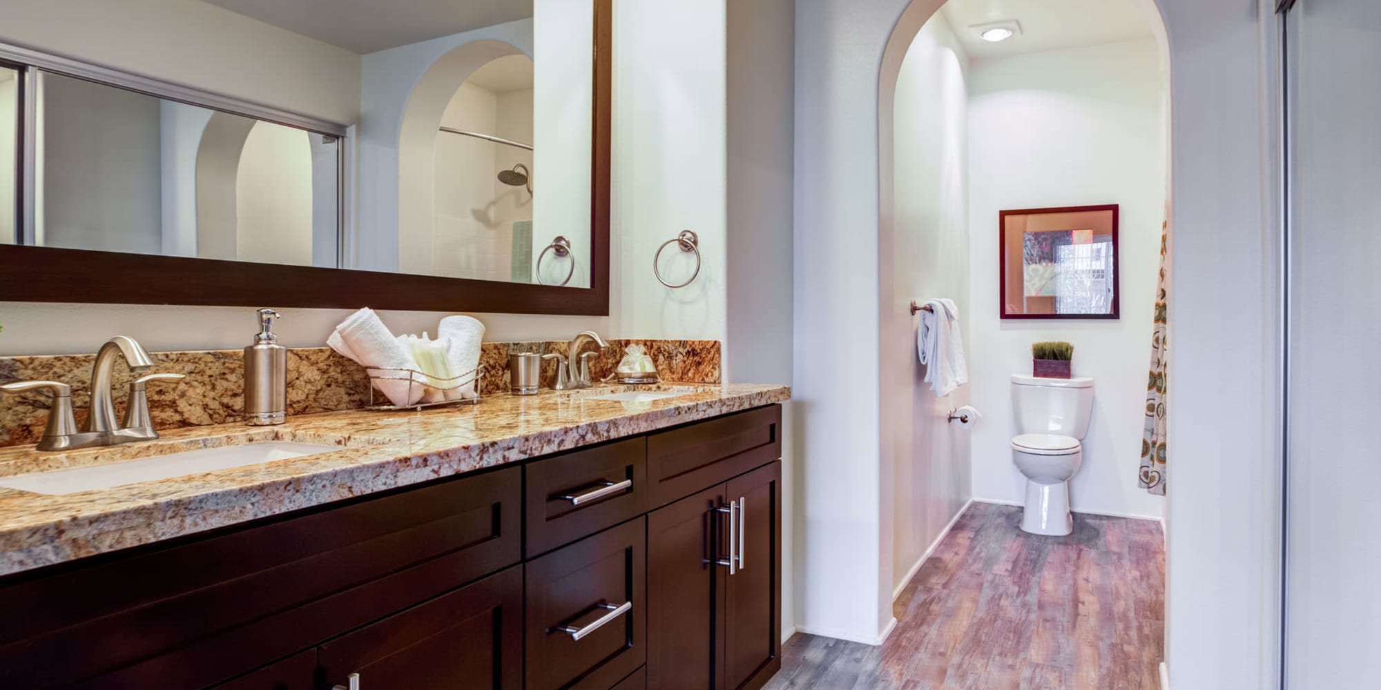 Large primary suite's bathroom with hardwood flooring in a model home at Granite countertop and an overside vanity mirror in a model apartment's bathroom at L'Estancia in Studio City, California