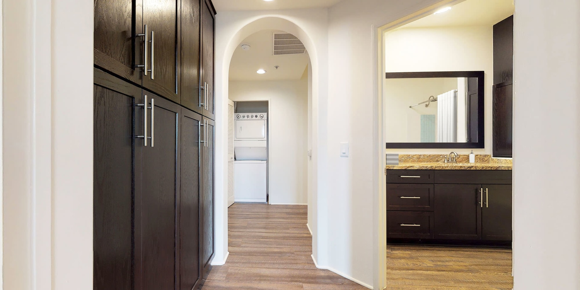 Espresso wood cupboard for extra storage in a model home's hallway leading to the stacked in-home washer and dryer at L'Estancia in Studio City, California