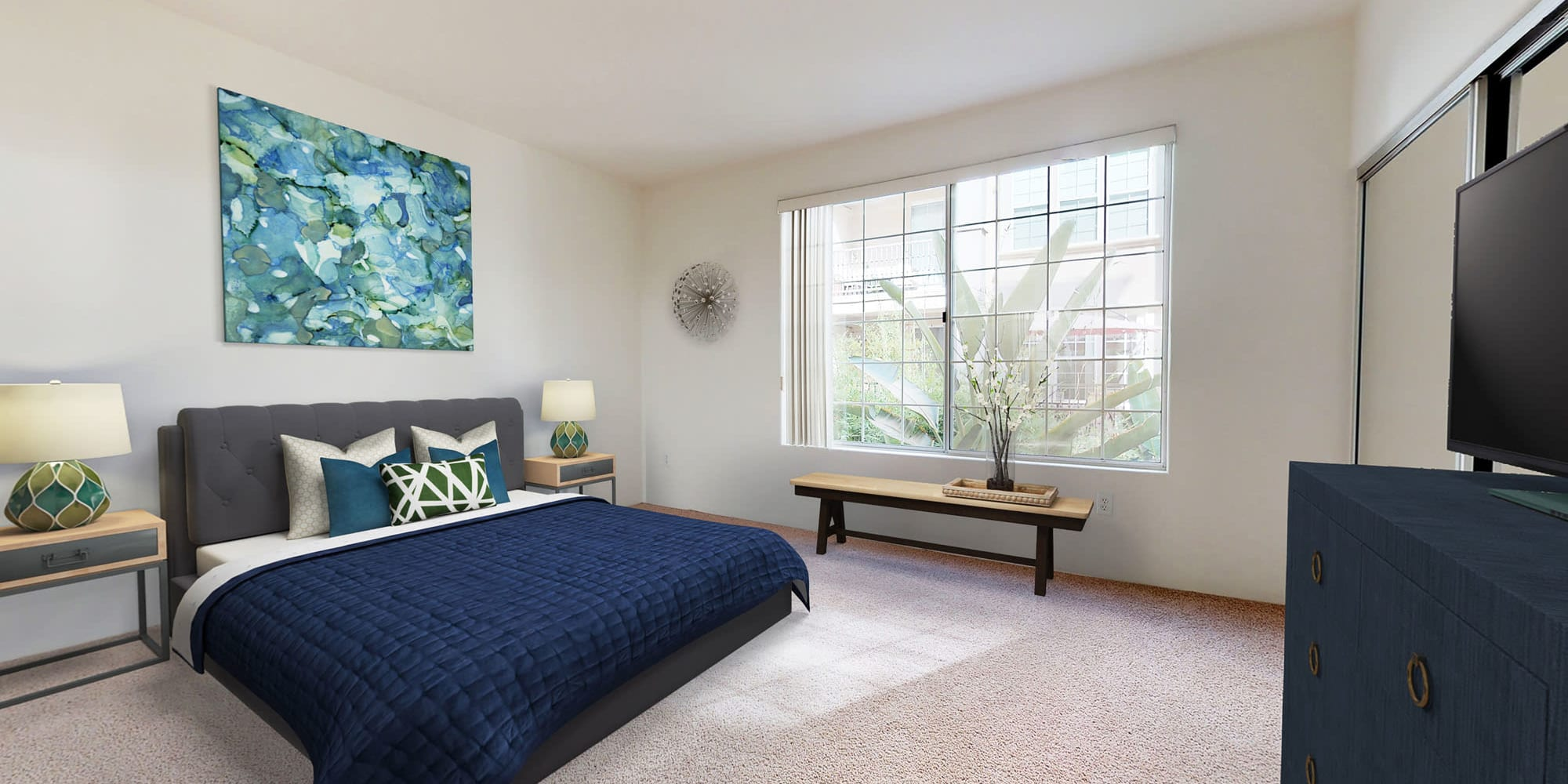 Model luxury home's primary suite with large bay windows and plush carpeting at L'Estancia in Studio City, California