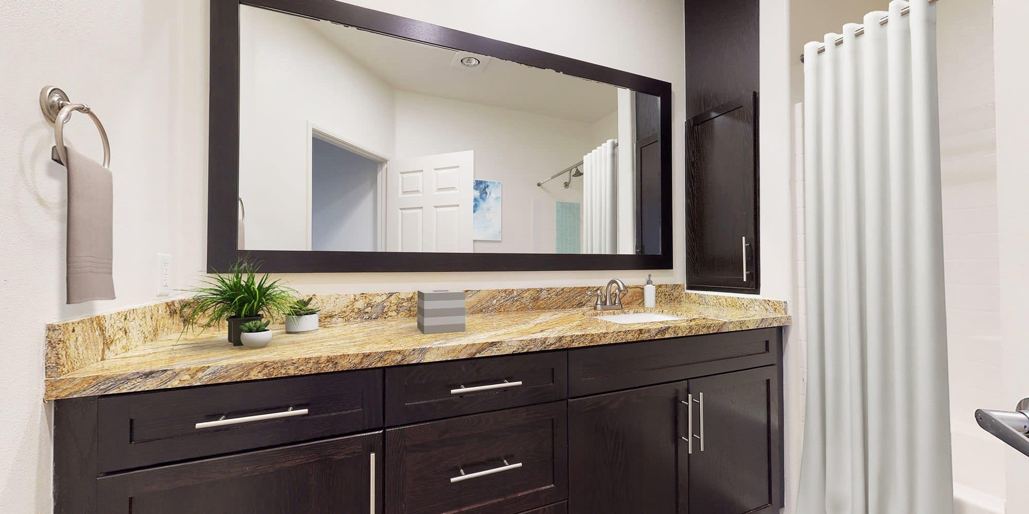 Granite countertop and an overside vanity mirror in a model apartment's bathroom at L'Estancia in Studio City, California