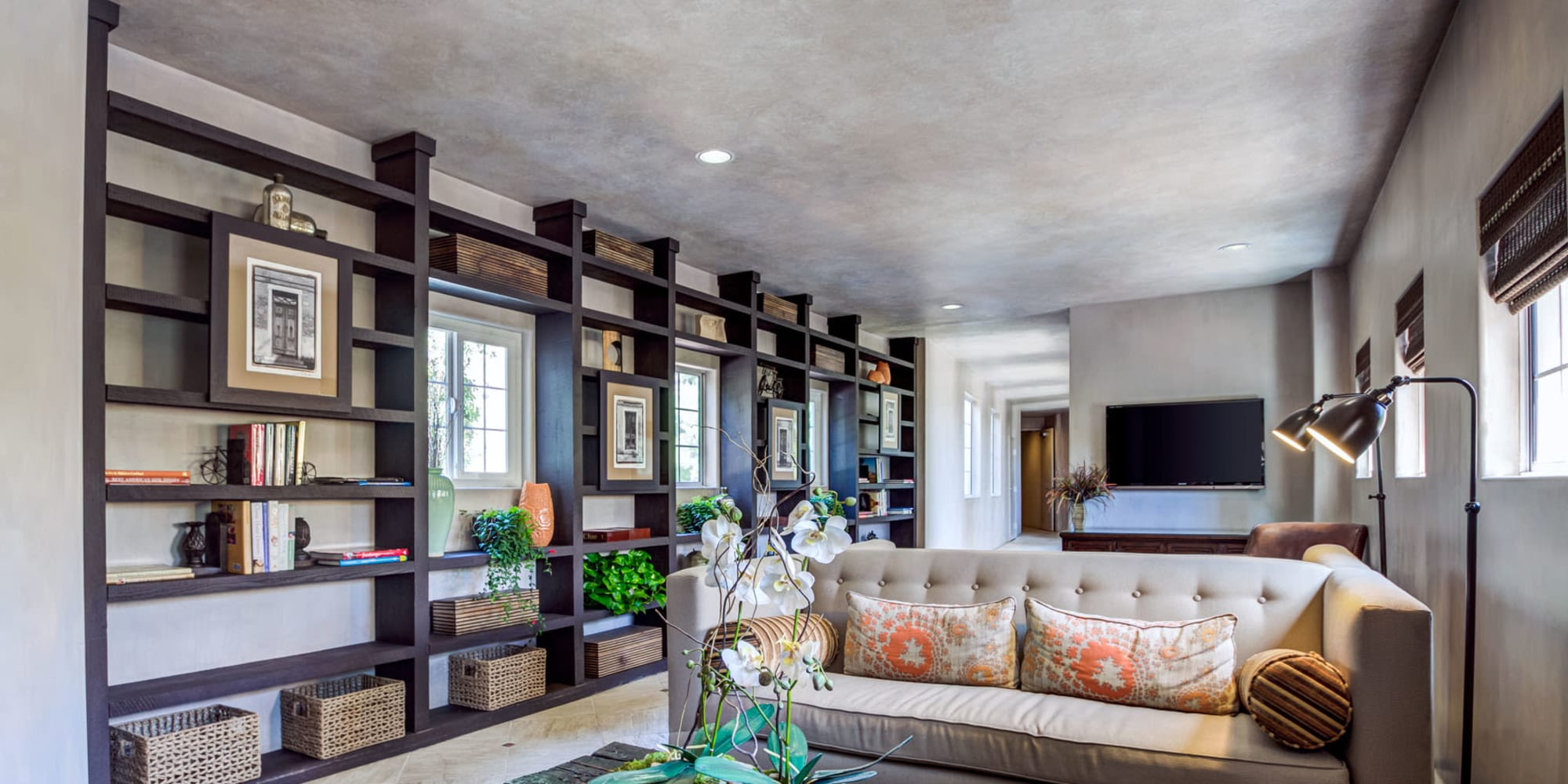 Custom built-in shelving with books and artwork in the lounge area of the resident clubhouse at L'Estancia in Studio City, California