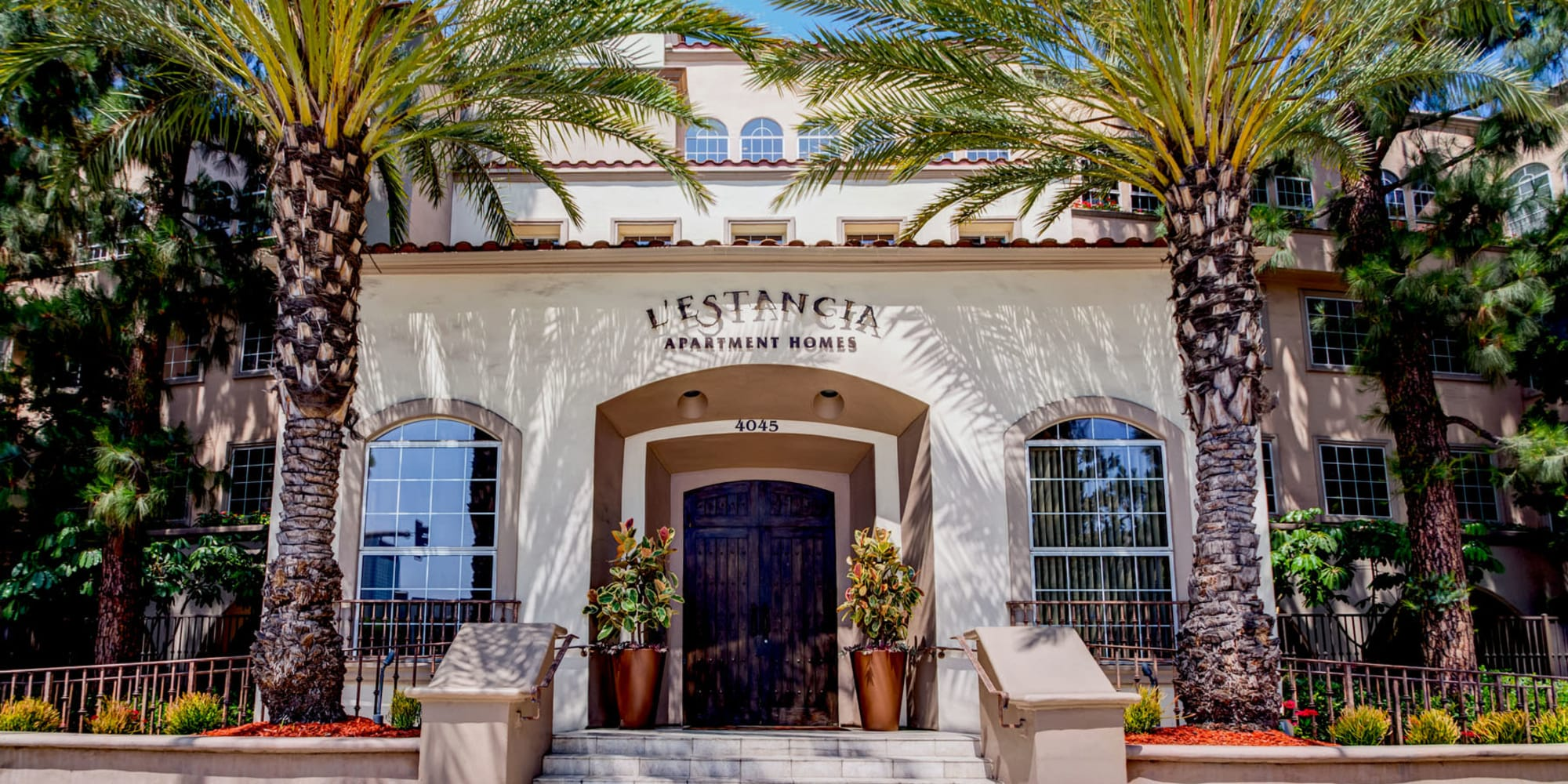 Palm trees and professionally maintained landscaping outside the entrance to L'Estancia in Studio City, California