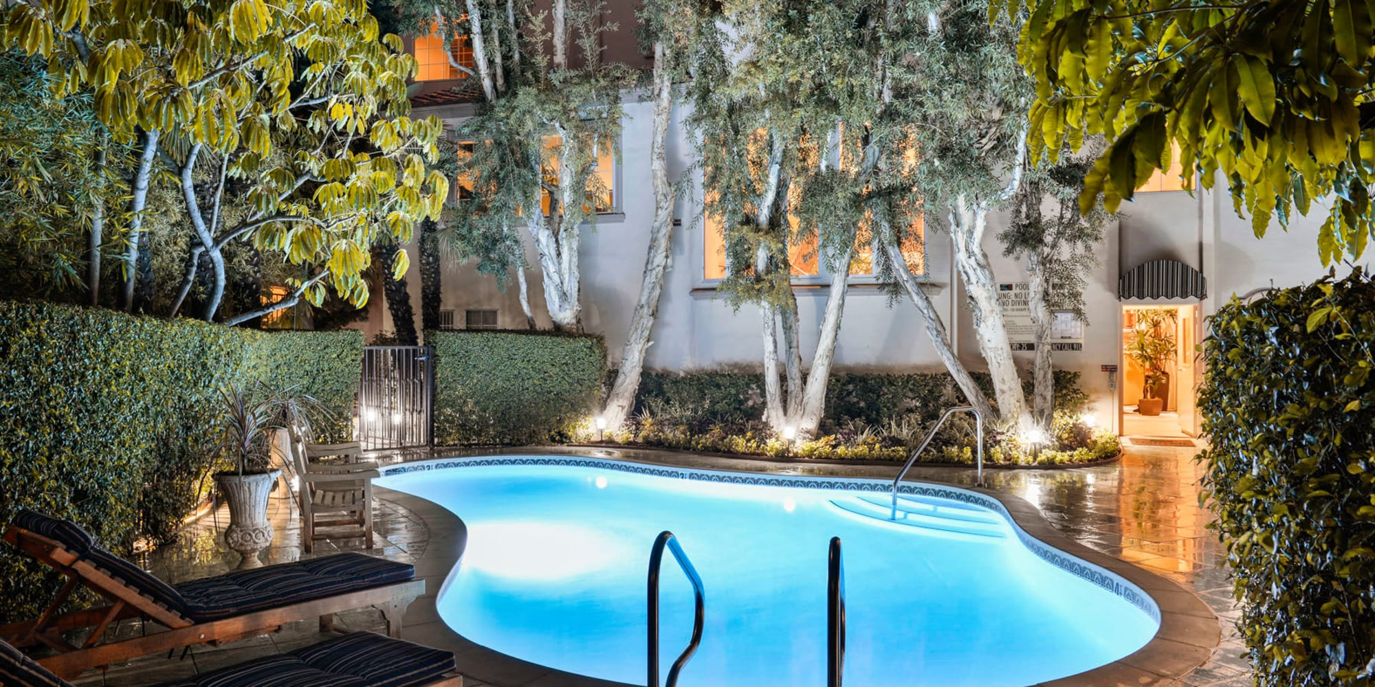 Underwater lights illuminating one of the swimming pools in the early evening at L'Estancia in Studio City, California