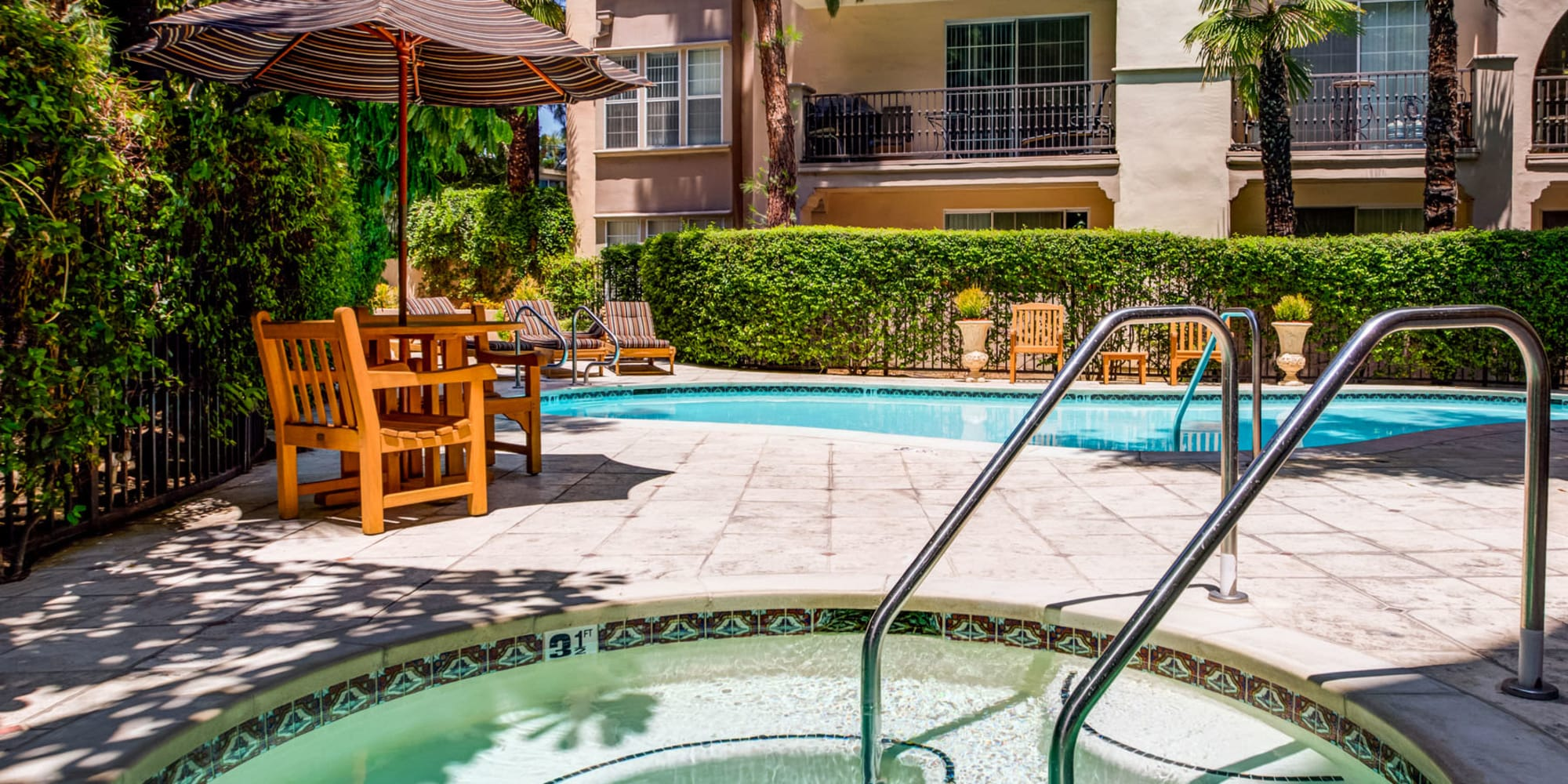 Swimming pool and spa area surrounded by lush landscaping and great places to relax at L'Estancia in Studio City, California