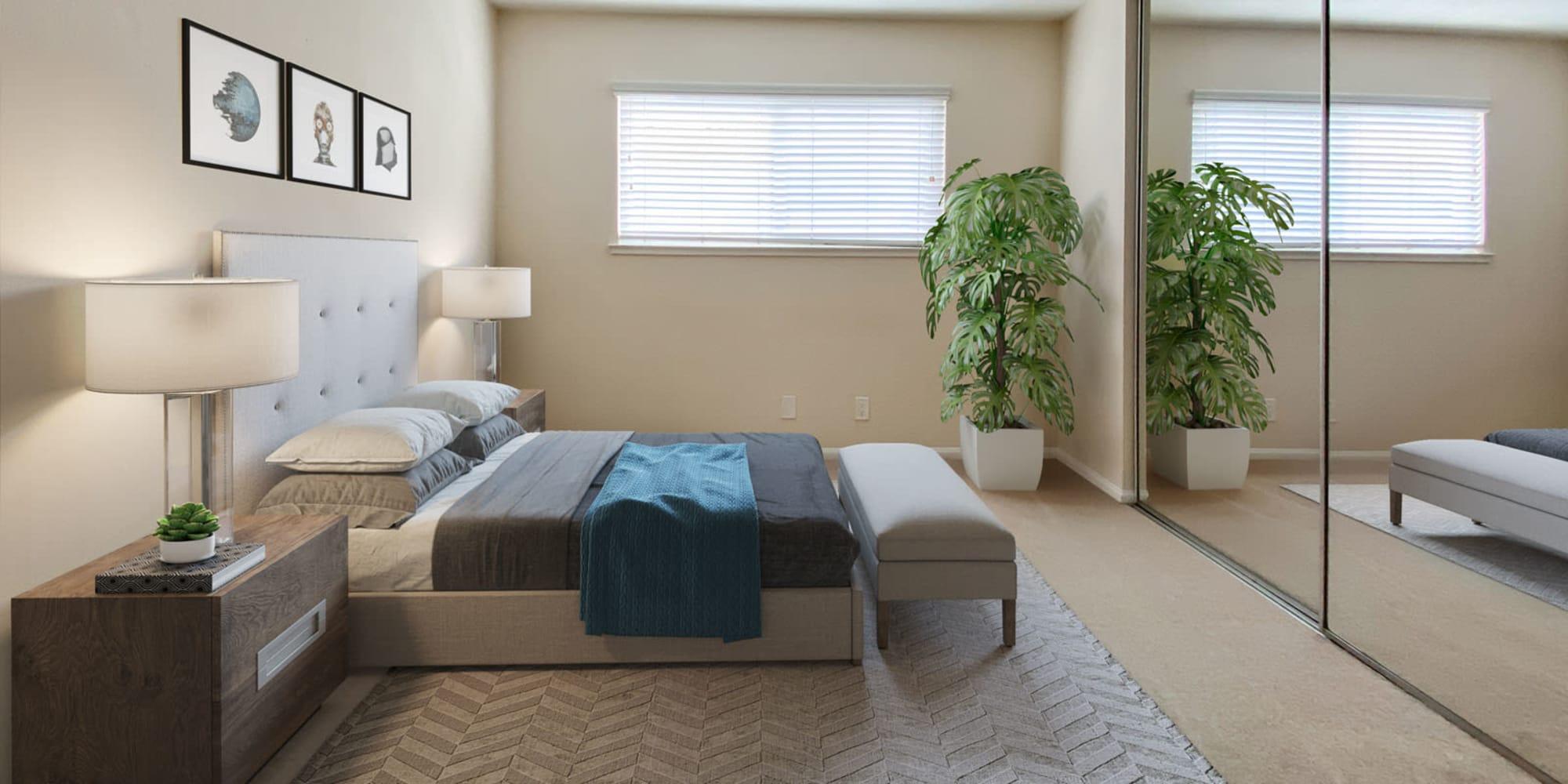 Mirrored closet doors in a model apartment's primary bedroom at Pleasanton Place Apartment Homes in Pleasanton, California
