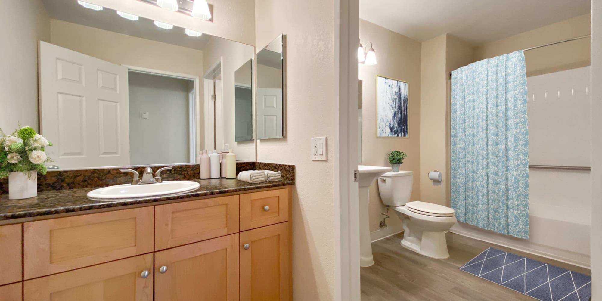 Primary bedroom's en suite bathroom with a large vanity mirror in a model home at Pleasanton Place Apartment Homes in Pleasanton, California