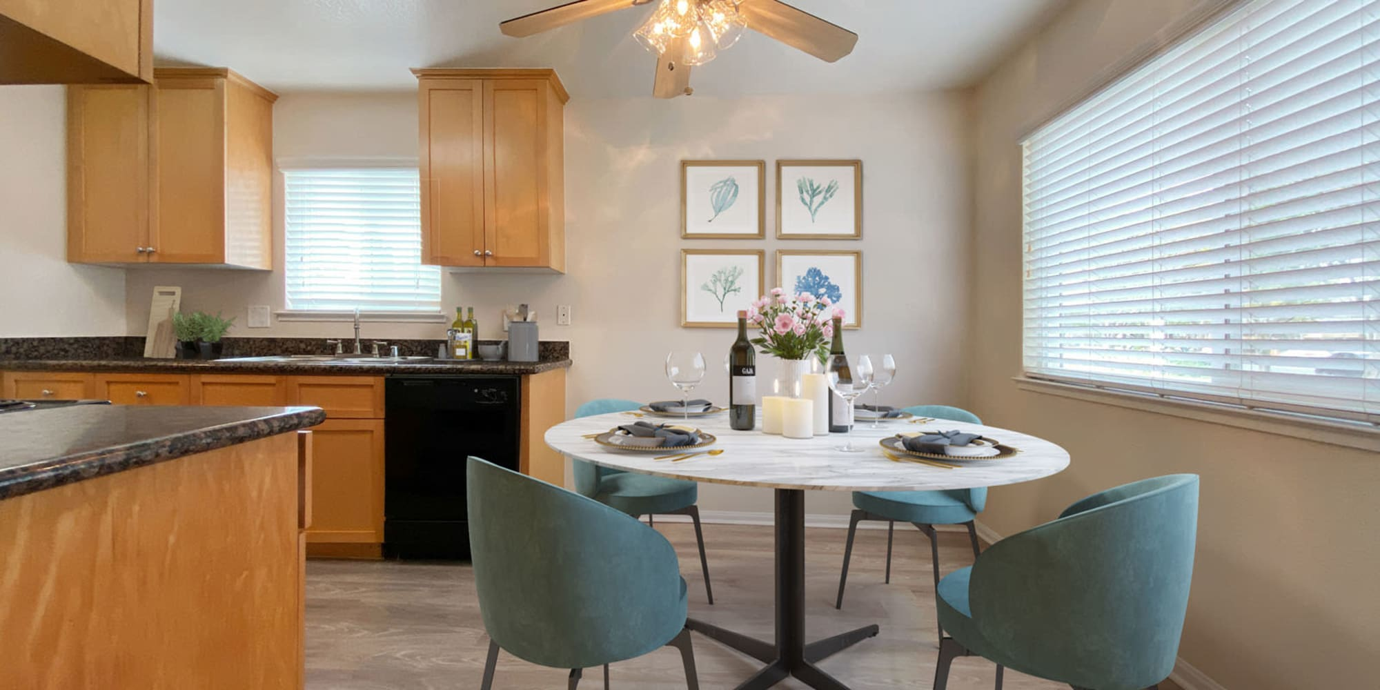 Dining nook with a ceiling fan overhead next to a model home's kitchen at Pleasanton Place Apartment Homes in Pleasanton, California