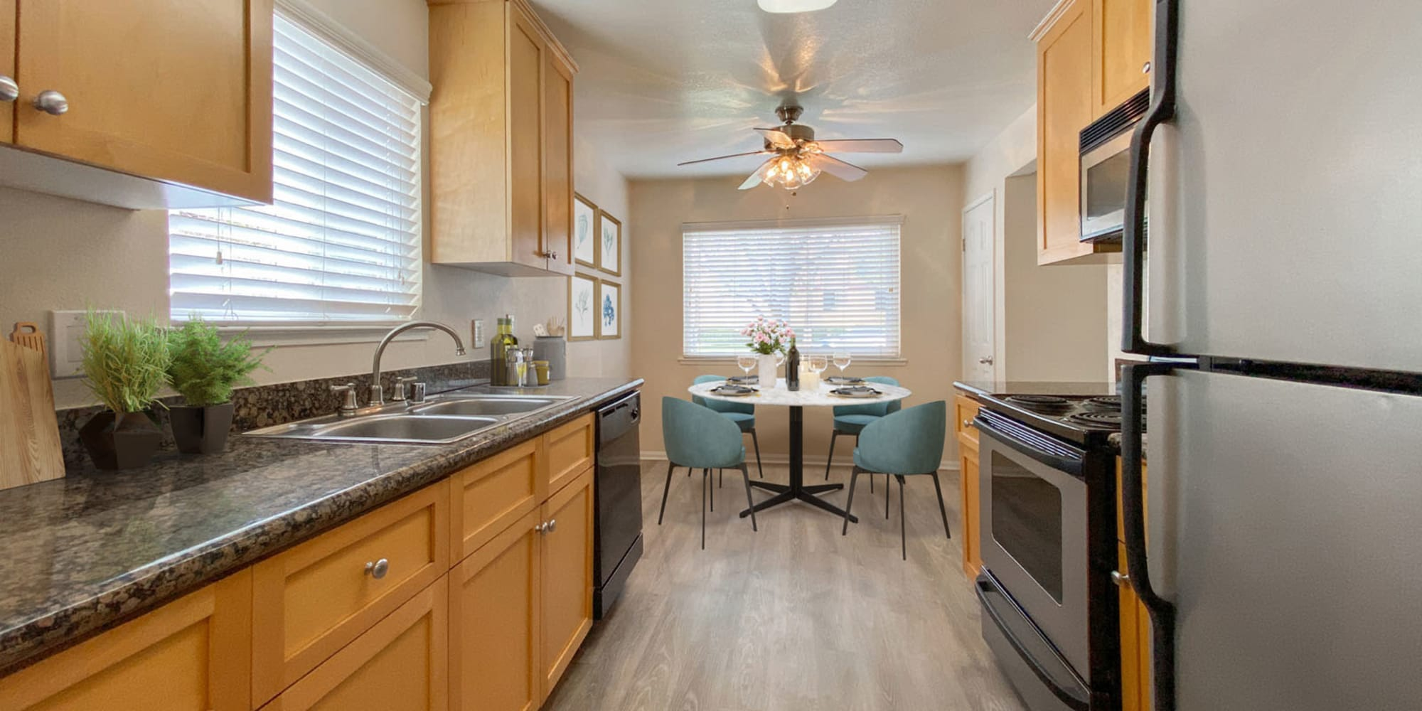 View of the dining nook from a model home's kitchen featuring stainless-steel appliances and hardwood flooring at Pleasanton Place Apartment Homes in Pleasanton, California