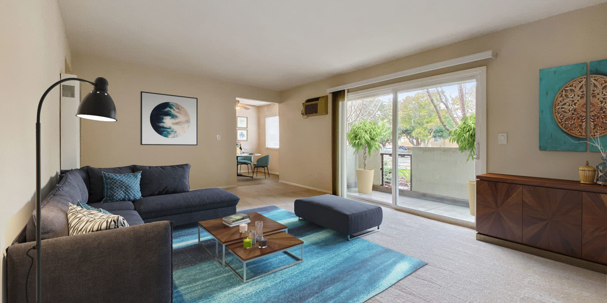 Comfortably furnished apartment home's living area with a view of the private balcony outside at Pleasanton Place Apartment Homes in Pleasanton, California