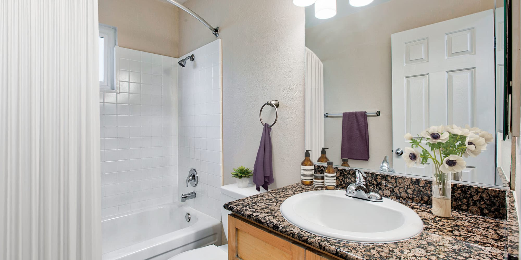 Tiled shower and a granite countertop in a model apartment's bathroom at Pleasanton Place Apartment Homes in Pleasanton, California